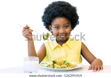 Close up portrait of cute african girl with afro hairstyle eating healthy vegetable dish. Isolated on white. #526395454
