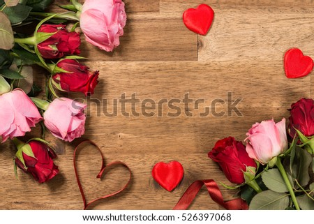 Roses  and red ribbon on wooden background. Valentines day background #526397068