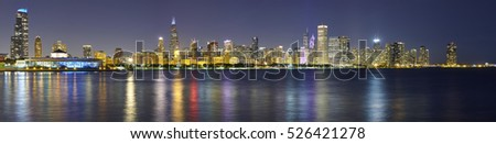 Night panoramic picture of Chicago city skyline with reflection in Lake Michigan.