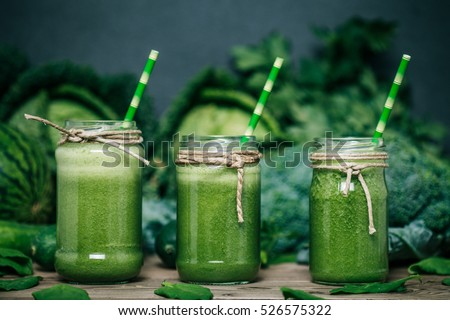 Blended green smoothie with ingredients on wooden table #526575322