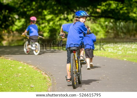 young happy preteen child boy riding a bicycle on natural park background, boy riding a bike in a park #526615795