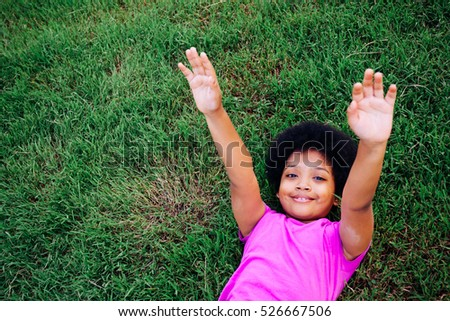 Little kid raising hands up and laying down on green grass in the park with copy space #526667506