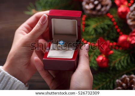 Christmas background. Engagement ring in female hands among Christmas decorations on wood background. Romance, jewelry concept - woman hands with wedding ring in gift box. Gift on Valentine's Day #526732309