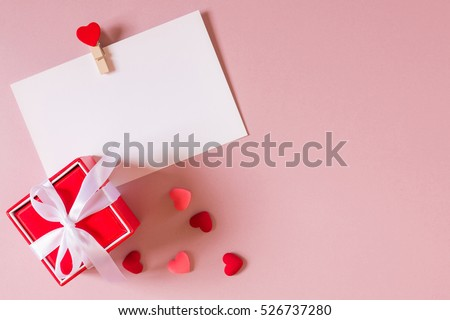 Valentine day composition: red gift box with bow, stationery / photo template with clamp and small hearts on light pink background. Top view. #526737280