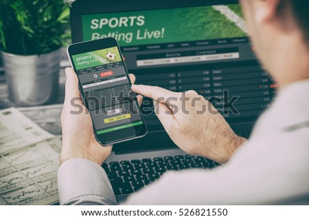 betting bet sport phone gamble laptop over shoulder soccer live home website concept - stock image Royalty-Free Stock Photo #526821550
