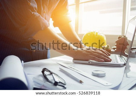 architect man working with laptop and blueprints,engineer inspection in workplace for architectural plan,sketching a construction project ,selective focus,Business concept vintage color Royalty-Free Stock Photo #526839118