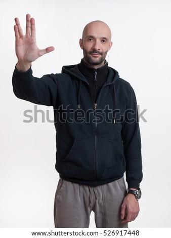 Caucasian man on white background making Star Trek hand signal