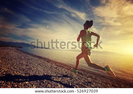 healthy lifestyle young woman runner running on sunrise seaside #526927039