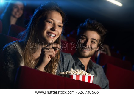 Young loving couple at the cinema watching a movie and smiling, people sitting on background #526930666