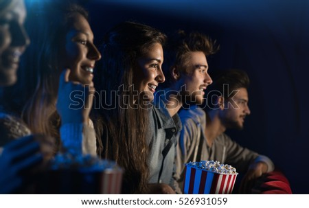 Group of teenager friends at the cinema watching a movie together and eating popcorn, entertainment and enjoyment concept #526931059