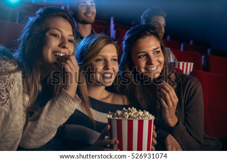 Smiling young girls sitting at the cinema, watching a film and eating popcorn, friendship and entertainment concept #526931074