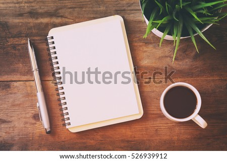 top view image of open notebook with blank pages next to cup of coffee on wooden table. ready for adding text or mockup. Retro filtered Royalty-Free Stock Photo #526939912