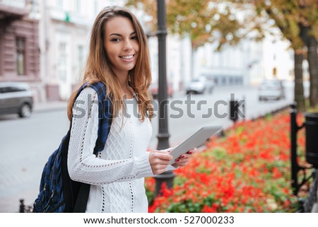 Smiling pretty young woman with backpack standing and using tablet in the city #527000233