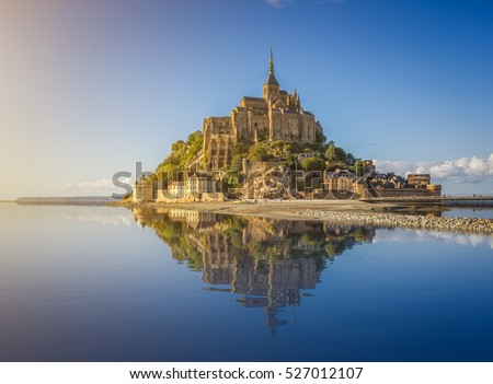 Beautiful panoramic view of famous Le Mont Saint-Michel tidal island with deep blue water and clear reflections in golden evening light at sunset in summer, Normandy, northern France #527012107
