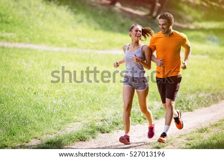 Couple jogging and running outdoors in nature #527013196
