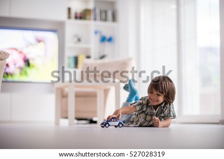 Happy kid playing with old car toy at home Royalty-Free Stock Photo #527028319