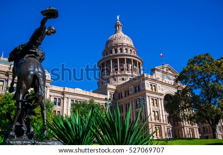 Riding a Horse to the Left of Texas State Capital building on a nice clear blue sky day with Sunlight hitting the Front of the capitol fresh green plants in the foreground with Government