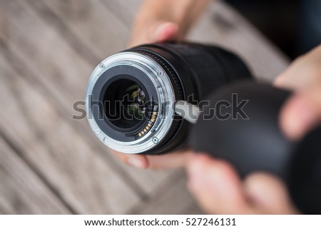 cleaning camera lens with air blower. #527246131