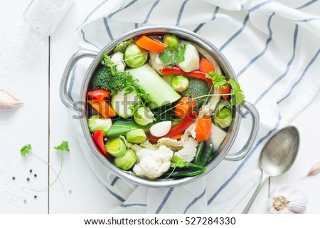 Various fresh vegetables in a pot - colorful fresh clear spring soup (vegetarian bouillon or stock). Rural kitchen scenery from above (top view). White rustic wooden background.