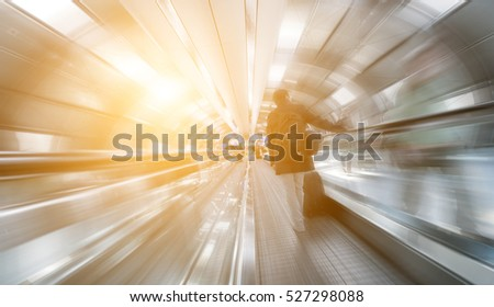 blurred passengers on a walkway tunnel #527298088
