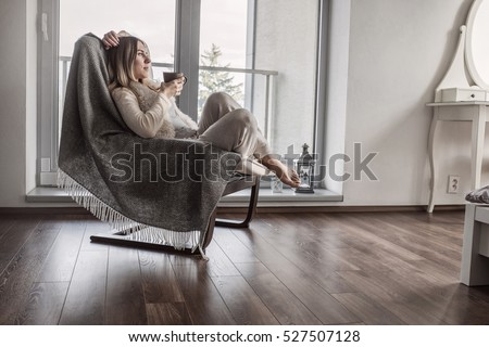 Woman drinks coffee and relax on vintage sofa at home near the window. Interior decoration in living room  #527507128