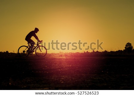 Abstract silhouette of men on mountain-bike with beautiful sky at sunset , As Abstract background. #527526523