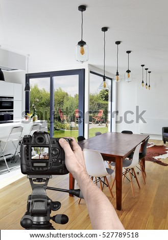Hands holding a professional camera on tripod taking picture in luxury living room