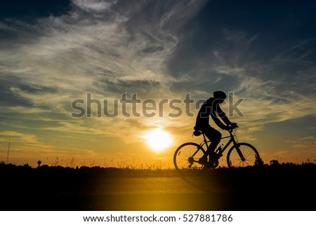 Abstract silhouette of men on mountain-bike with beautiful sky at sunset . #527881786