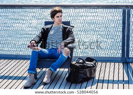 American man traveling in New York, wearing fashionable coat, striped shirt, ripped broken hole jeans, boots,  carrying duffel leather bag, sitting on dock by river, relaxing. Color filtered effect  #528044056