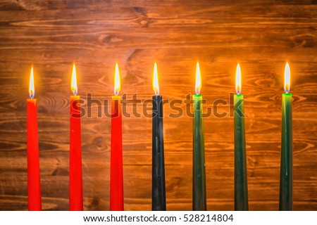 Kwanzaa festival concept with seven candles red, black and green on wooden background, close up