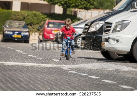 4-year old little Caucasian boy with a red polo shirt driving a bicycle with no helmet in dangerous proximity to cars and minivans on the street.  accident, children, child falling, road accident. #528237565