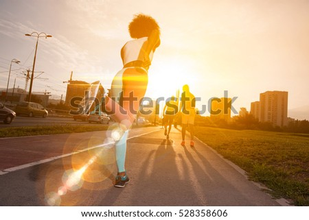 young black girl on the jogging beautiful morning as the sun rises in the streets of the city #528358606