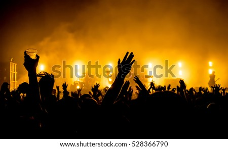silhouettes of concert crowd in front of bright stage lights #528366790