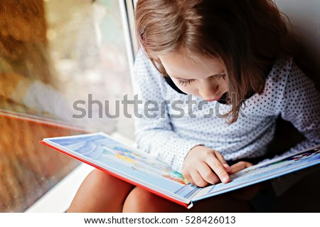 toddler girl with book near the window