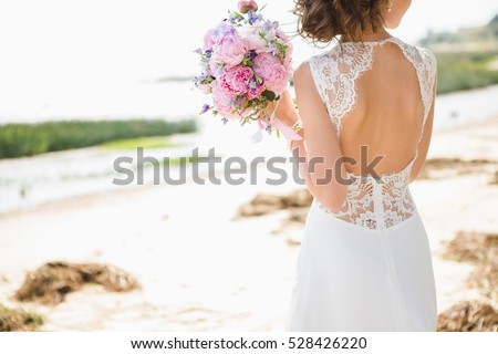 Bride on the coast of the sea, the wind. On the bride is a long wedding dress with lace and an open back. Royalty-Free Stock Photo #528426220