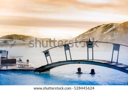 a couple under the bridge in the thermal blue lagoon, Iceland #528445624