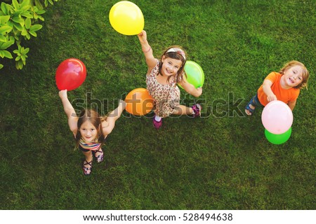 Three happy little kids playing with colorful balloons outdoors, top view #528494638