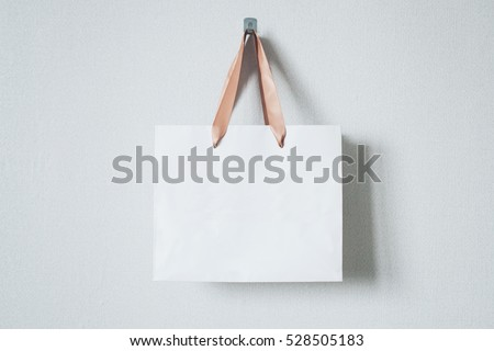 Mock-up of blank craft package, mockup of white paper shopping bag with handles on the neutral background Royalty-Free Stock Photo #528505183