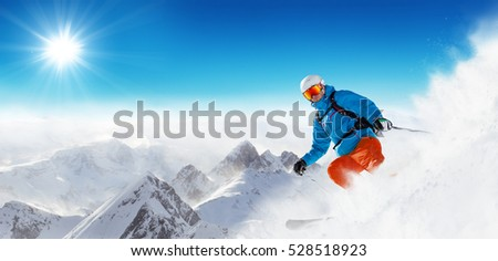 Skier on piste running downhill in beautiful Alpine landscape. Blue sky on background. Free space for text #528518923