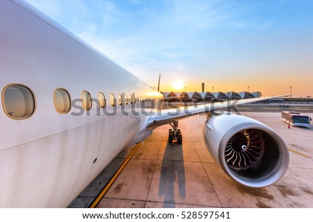 Airplane being preparing ready for takeoff in international airport at sunset - Travel around the world.