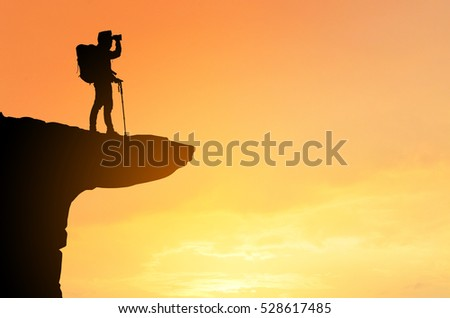 Hiking tourists standing on the rock ,beautiful mountain view, sunset background ,backpack silhouette   #528617485