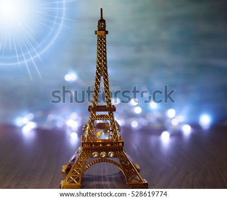 Miniature Eiffel Tower on the background of Christmas lights - soft focus #528619774
