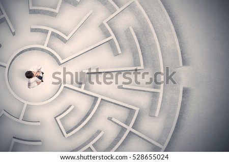 Confused business man trapped in a circular maze Royalty-Free Stock Photo #528655024