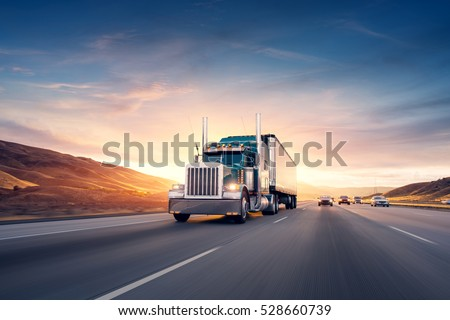American style truck on freeway pulling load. Transportation theme. Road cars theme. Royalty-Free Stock Photo #528660739