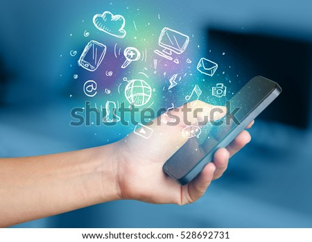 Hand holding smartphone with glowing multimedia icons  #528692731