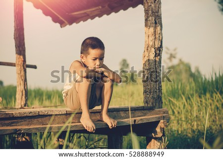 Little boy unhappy sitting alone on abandoned temporary housing. #528888949