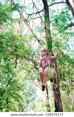 adventure climbing high wire park - hiking in the rope park girl in safety equipment #528934171
