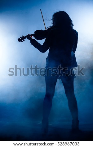 Silhouette of a Rock Woman with Leather Jacket Playing a Violin #528967033
