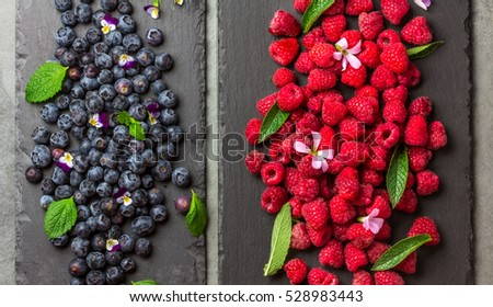 Berry raspberries and blueberries with fresh mint leaves and edible flowers on black slate board. Mix of berries, healthy food,diet,detox concept. Top view. #528983443