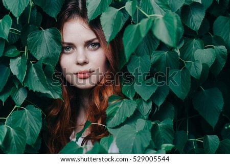 woman in green leaves enjoying nature.  #529005544